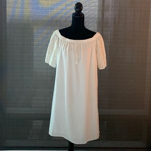 White peasant dress with embroidered sleeves.